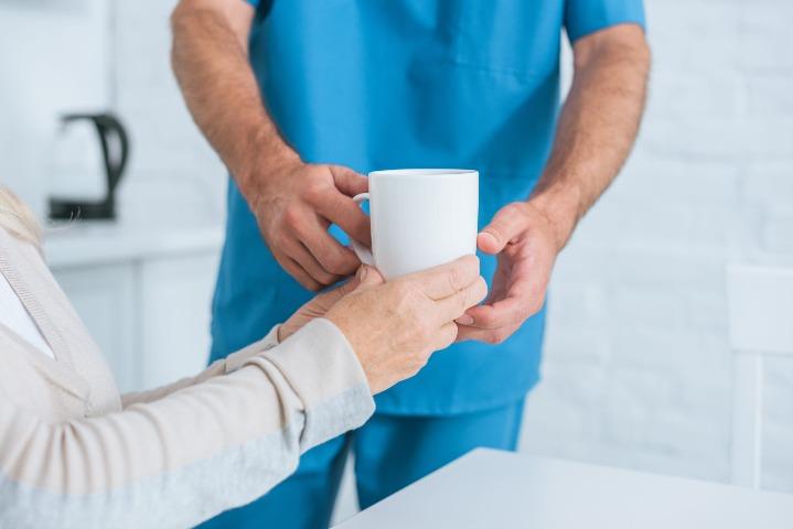 Caregiver gibing Woman Some Tea
